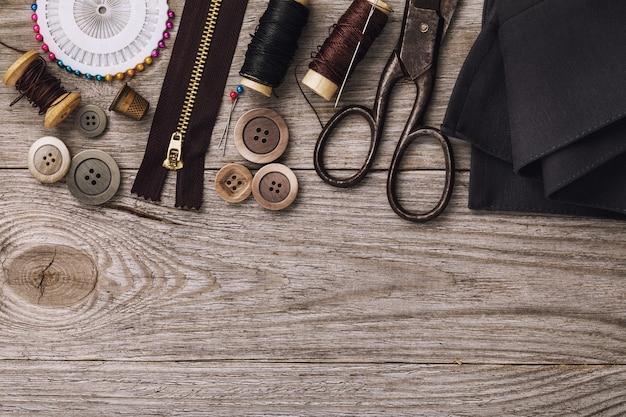 Ferramentas para consertar e costurar roupas em mesa de madeira com espaço de cópia