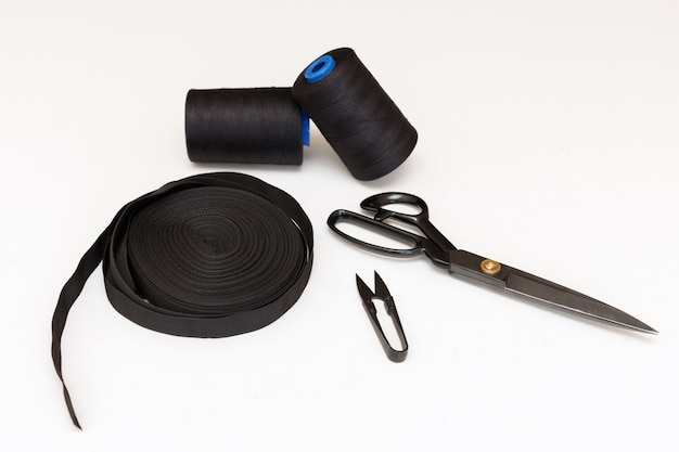 Ferramentas para costura em fundo homogêneo. tesouras, fios e fita adesiva. bordado e hobbies