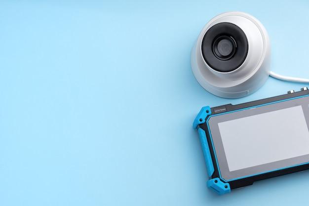 Ferramentas para instalação de vigilância por vídeo. câmera de segurança e monitor de testador cctv em um fundo azul com espaço para texto. vista do topo. copie o espaço.