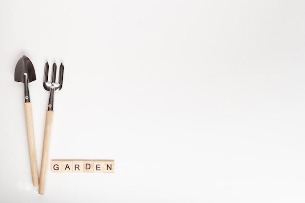 Ferramentas para jardinagem em casa e texto jardim feito de cubo de madeira