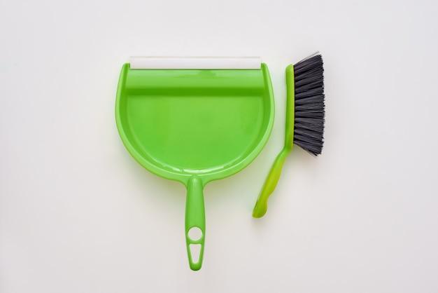 Ferramentas para limpar o chão. escovar e colher isoladas no fundo branco Foto Premium