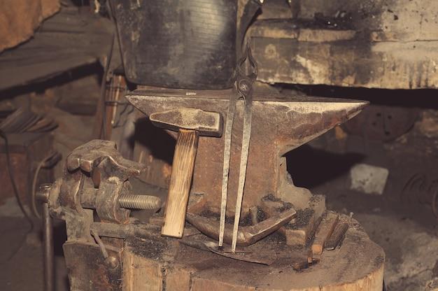 Ferramentas para martelo de metal na bigorna na ferraria