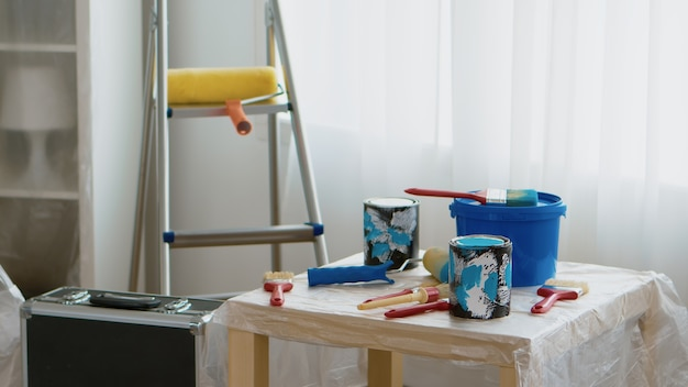 Ferramentas para renovação doméstica. latas de tinta, pincel, rolo. casa durante a reforma, decoração e pintura. manutenção de melhorias no interior do apartamento. rolo, escada para conserto de casa