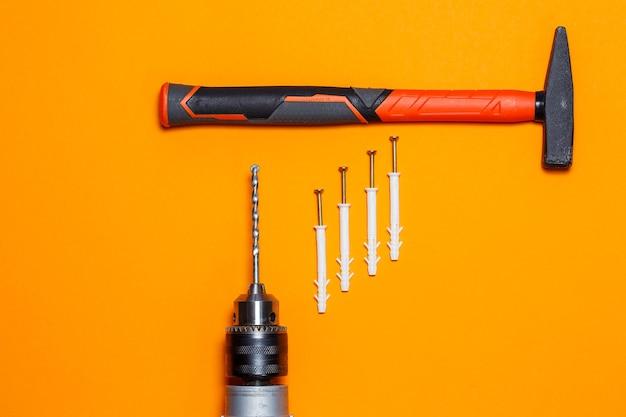Ferramentas para reparo. martelo para pregos, broca, cavilha na parede em um fundo laranja. kit de ferramentas para o assistente