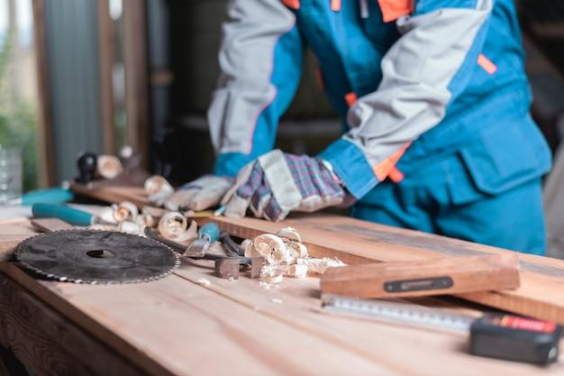 Ferramentas para trabalhar madeira em cima da mesa no fundo dos homens no trabalho em borrão, foco seletivo