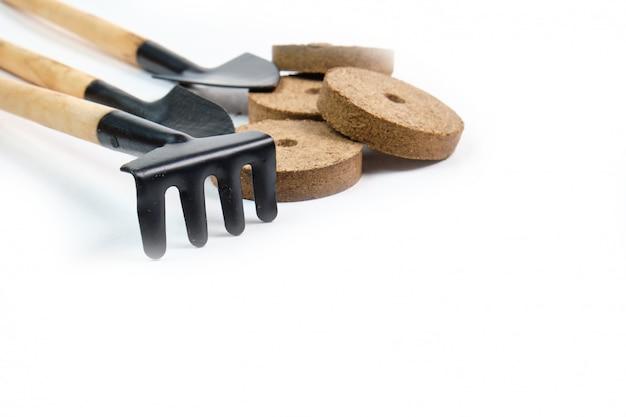 Ferramentas, sementes, vasos de turfa e terra prensada para mudas