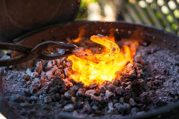 Ferreiro fazendo uma ferradura na pequena forja.