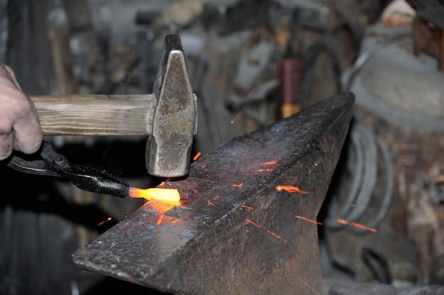 Ferreiro trabalhando metal com martelo na bigorna na forja