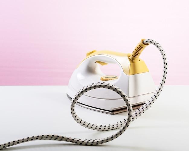 Ferro de alisar vapor amarelo em fundo rosa. objeto único com traçado de recorte