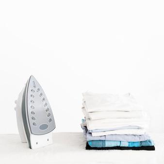Ferro de passar roupas ao lado de roupas empilhadas