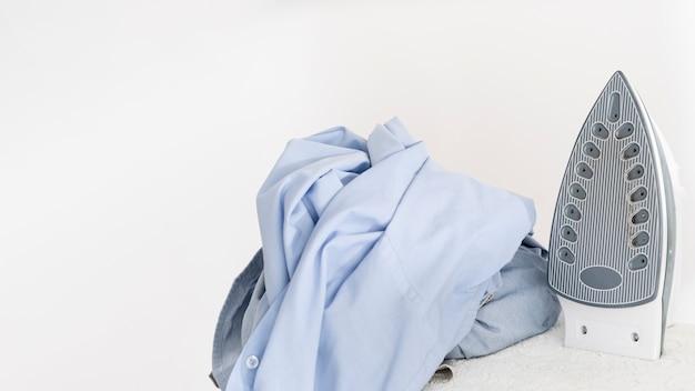 Ferro de passar roupas ao lado de roupas