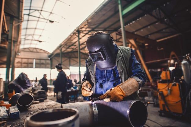Ferro de solda do trabalhador. traje de proteção e máscara. interior da oficina.
