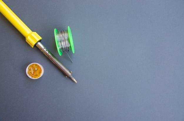 Ferro de solda, estanho, resina sobre uma mesa preta. ferro de soldar nas mãos masculinas. reparação de equipamentos elétricos, engenharia de rádio. fios de solda, contatos.