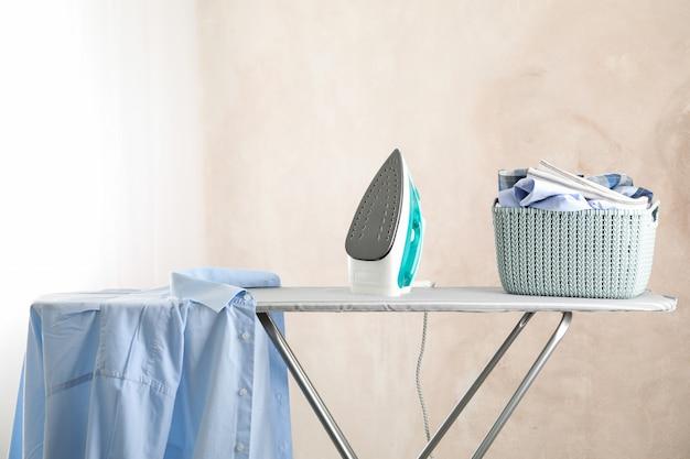 Ferro e cesto com roupa limpa contra a luz,