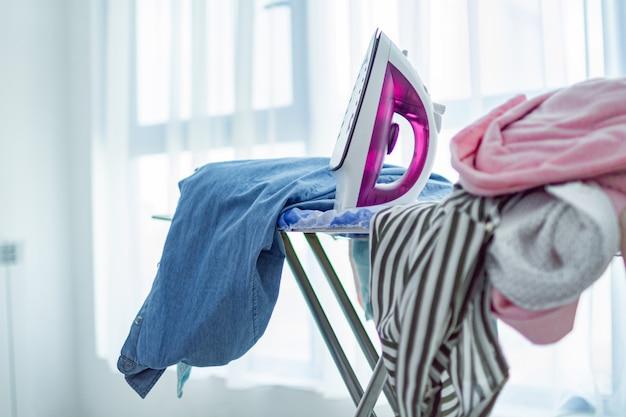 Ferro e pilha de roupas limpas