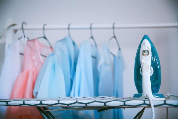 Ferro e roupas modernos em salão de lavagem a seco azul