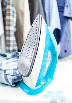 Ferro elétrico e camisa, em pano