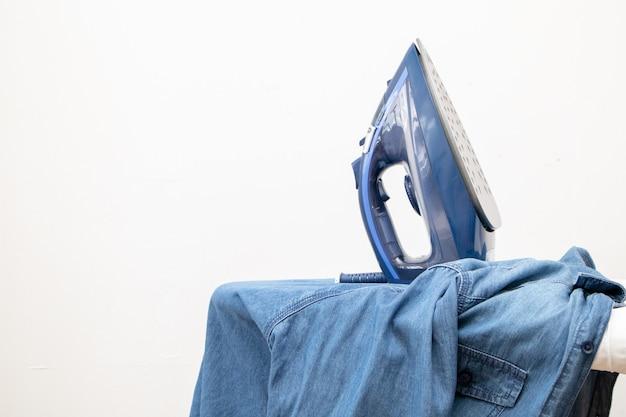 Ferro elétrico e camisa jeans azul na tábua de passar