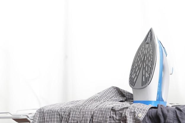 Ferro elétrico e pilha de roupas na tábua e fundo branco