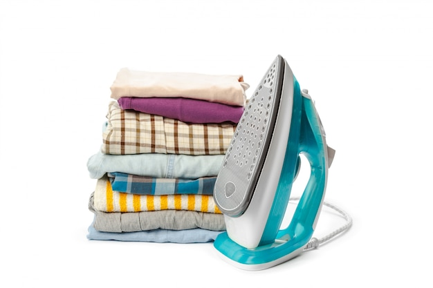 Ferro elétrico e pilha de roupas.