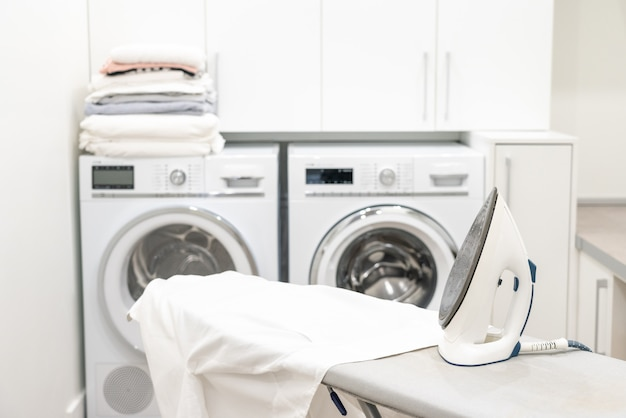 Ferro na tábua de passar roupa com camisa branca na lavanderia
