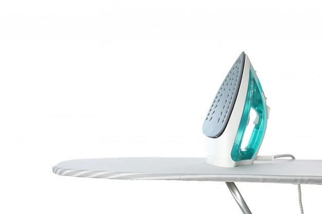 Ferro na tábua de passar roupa isolado no branco