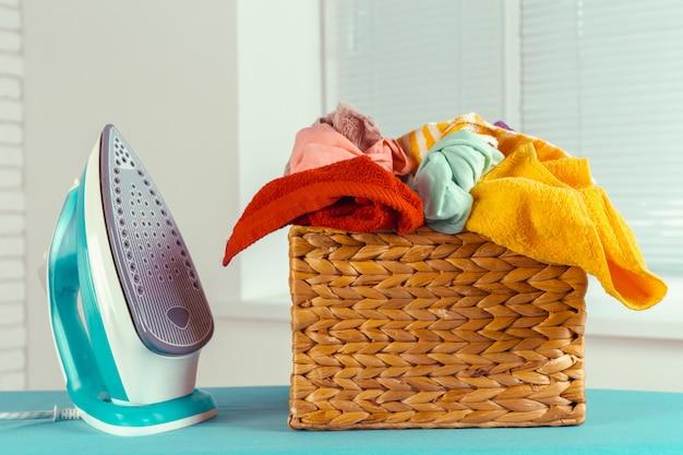 Ferro na tábua de passar roupa na luz de fundo interior de casa