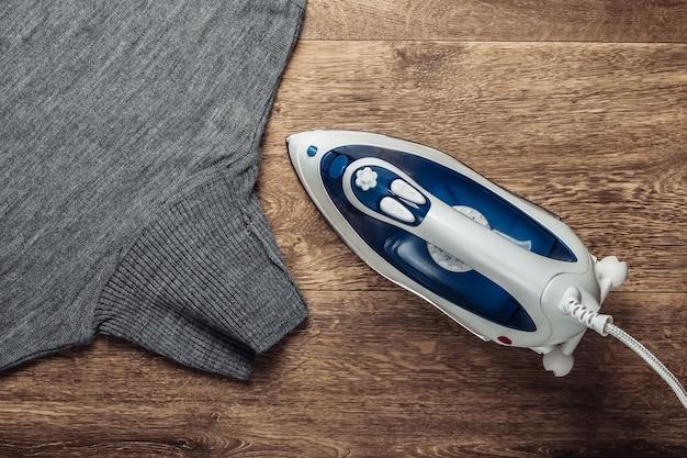 Ferro para engomar, roupa no chão. conceito de vida doméstica. vista do topo