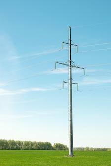 Ferro que carrega linhas elétricas de alta tensão em um campo verde.