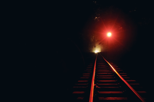 Ferrovia à noite. a luz vermelha está acesa.