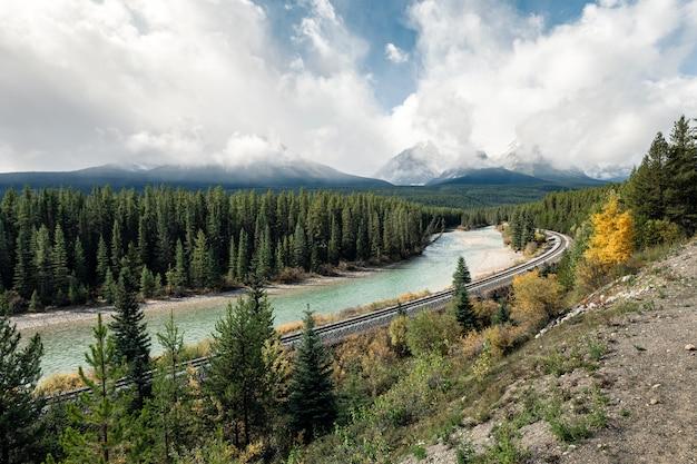 Ferrovia com montanhas rochosas e céu nublado no vale do outono na curva de morant, calgary, canadá