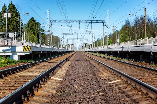 Ferrovia com plataformas em uma estação provincial. trilhos metálicos e dormentes. viagem e turismo. parede. espaço para texto.