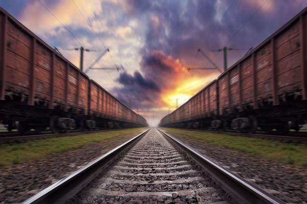 Ferrovia em movimento com efeito de desfoque ao pôr do sol com céu dramático.