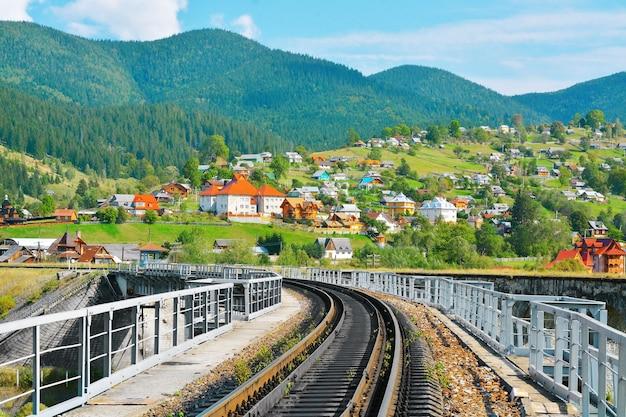 Ferrovia pela aldeia nas montanhas