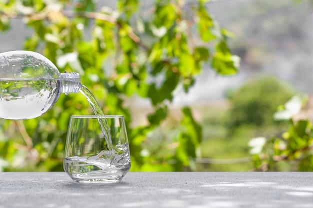 Fersh, limpar, beber água derramando em um copo de uma garrafa de plástico no fundo borrado da natureza. Foto Premium