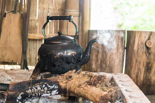 Ferva a água na velha chaleira de alumínio na lenha queima.