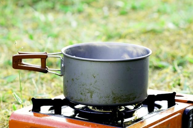 Ferva algo em panela no fogão a gás na grama para camping