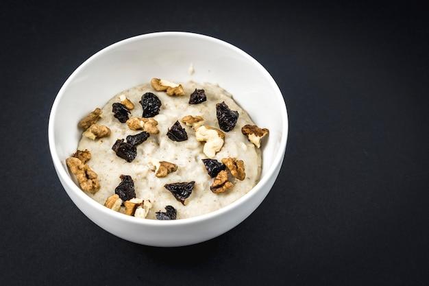 Fervemos o leite com a aveia e adicionamos ameixas e nozes. receita de aveia com nozes, ameixas, canela e açúcar.