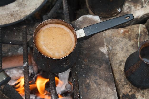 Fervendo café em cezva turco em uma grelha sobre uma fogueira ardente, um conceito de campismo