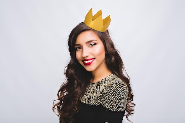 Festa à noite, aniversário, celebração de ano novo. retrato alegre de menina bonita com cabelo castanho longo encaracolado na coroa amarela no espaço em branco