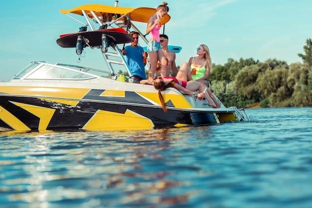 Festa a todo vapor. grupo de jovens despreocupados segurando bebidas não alcoólicas durante uma festa em um barco de recreio