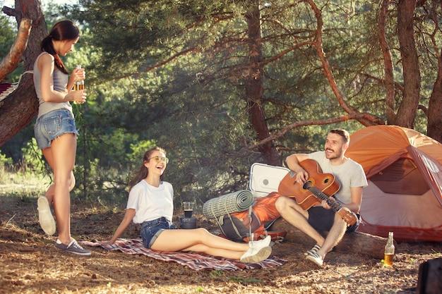 Festa, acampamento de grupo de homens e mulheres na floresta. eles relaxam, cantando uma música contra a grama verde. as férias, verão, aventura, estilo de vida, conceito de piquenique