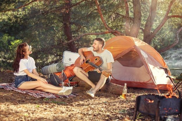 Festa, acampamento de grupo de homens e mulheres na floresta. eles relaxam, cantando uma música contra a grama verde. conceito