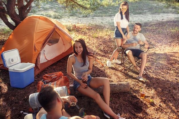 Festa, acampamento de grupo de homens e mulheres na floresta. eles relaxam contra a grama verde. as férias, verão, aventura, estilo de vida, conceito de piquenique