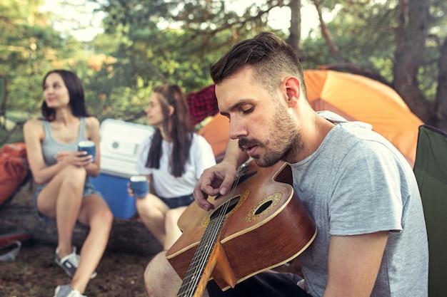 Festa, acampamento de grupo de homens e mulheres na floresta. relaxando, cantando uma música contra a grama verde.