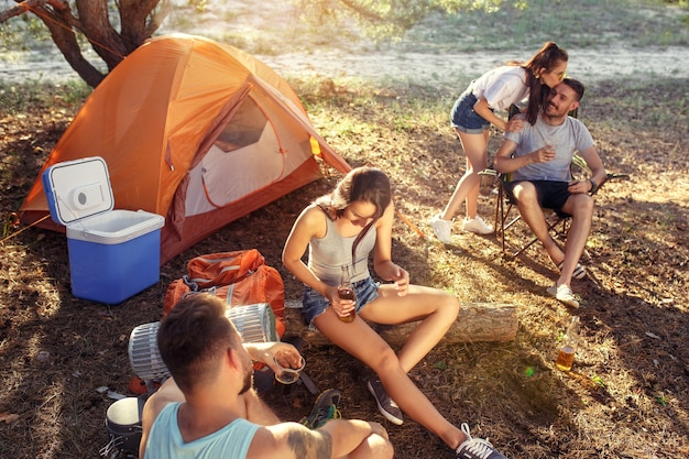 Festa, acampamento de grupo de homens e mulheres na floresta