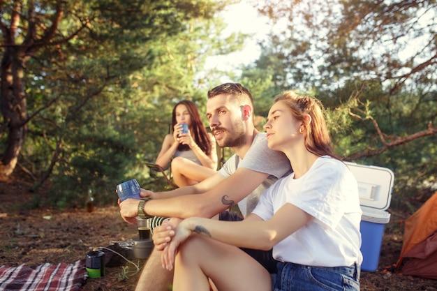 Festa, acampamento de homens e mulheres do grupo na floresta. eles relaxando
