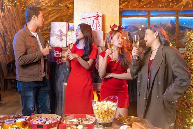 Festa alegre amigos asiáticos curtindo bebidas de natal e comemorando com selfie pelo smartphone
