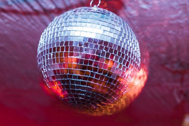 Festa com bola de discoteca com luzes vermelhas