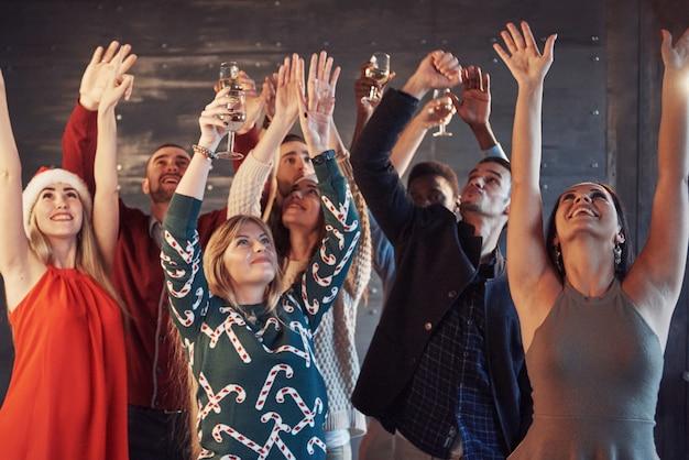 Festa com os amigos. eles amam o natal. grupo de jovens alegres carregando estrelinhas e taças de champagne dançando na festa de ano novo e olhando feliz. conceitos sobre estilo de vida de união